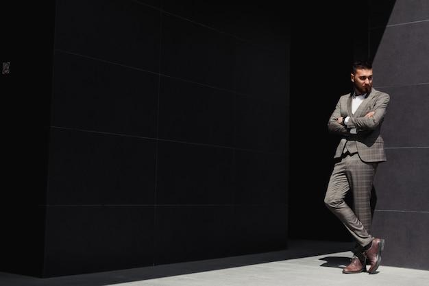 Elegancko ubrany biznesmen, nowoczesny biznesmen. przekonany, młody człowiek w pełnym garniturze stojący na zewnątrz z budynkiem w tle
