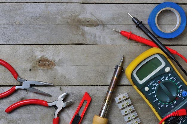 Elektronarzędzie i tester na drewnianym tle. kopiuj przestrzeń