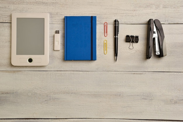 Elektroniczna książka, pamięć flash, notatnik, długopis, segregator i zszywacz leżą na beżowym drewnianym stole.