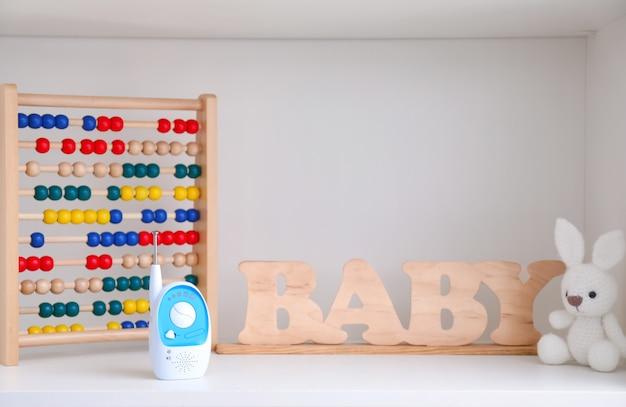 Elektroniczna niania, zabawki i drewniane litery na półce