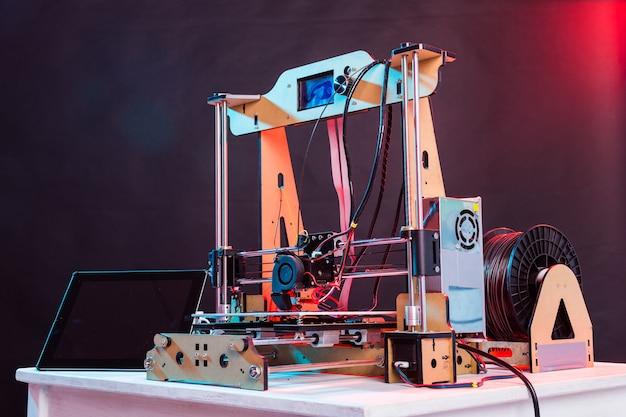 Elektroniczna trójwymiarowa drukarka plastikowa podczas pracy w szkolnym laboratorium, drukarka 3d, druk 3d.