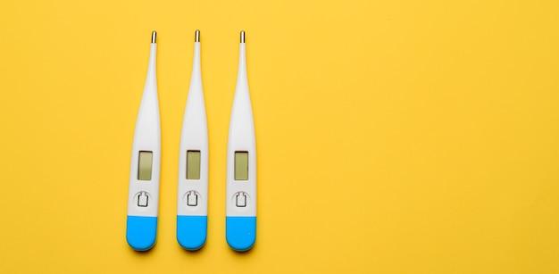 Elektroniczne termometry na żółtej powierzchni