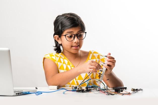 Elektroniczny eksperyment - azjatycka indyjska mała studentka wykonująca lub studiująca naukę z przewodami, połączeniami, ucząca się na laptopie lub tablecie