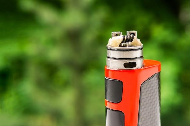 Elektroniczny papieros na tle drzew, widoczna spiralna wełna i para.