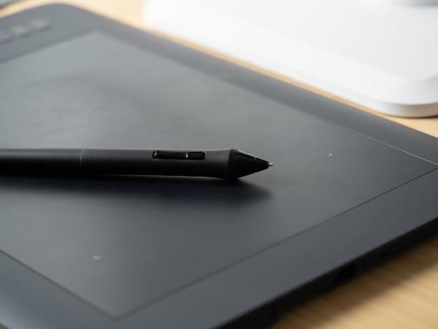 Elektroniczny tablet z leżącym na nim graficznym piórem. idealne narzędzie dla projektantów