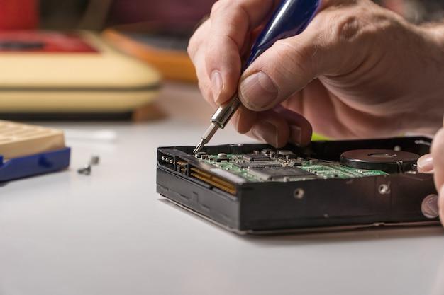 Elektronik naprawia dysk twardy komputera. technolog ze śrubokrętem demontuje hdd