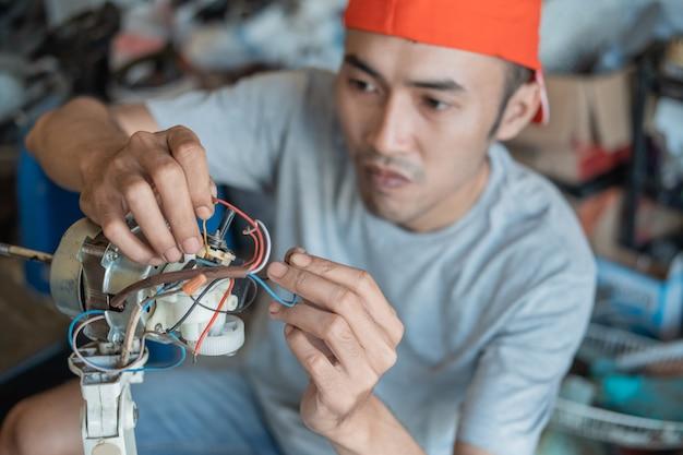 Elektronik naprawia uszkodzony przewód w zepsutym wentylatorze w warsztacie elektronicznym