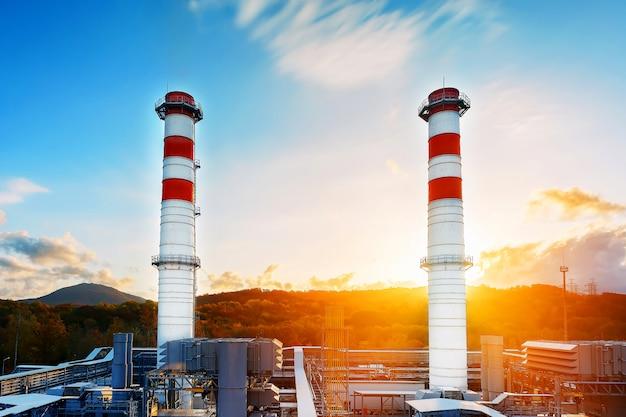Elektrownia gazowa z dwoma długimi rurami w kolorze białym z czerwonymi poloskai na górach i wschodzie słońca.