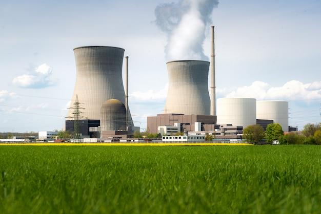 Elektrownia jądrowa z żółtym polem i dużymi niebieskimi chmurami.