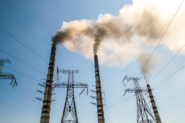 Elektrownia przemysłowa opalana węglem ze stosami dymu. brudny dym na niebie, problemy ekologiczne.