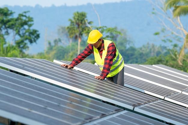 Elektrownia słoneczna, inżynier pracujący nad sprawdzaniem i konserwacją paneli fotowoltaicznych w elektrowni słonecznej, nauka o energii słonecznej.