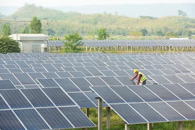 Elektrownia słoneczna, panele słoneczne z technikiem, przyszła produkcja elektryczna, inżynierowie azjatyccy
