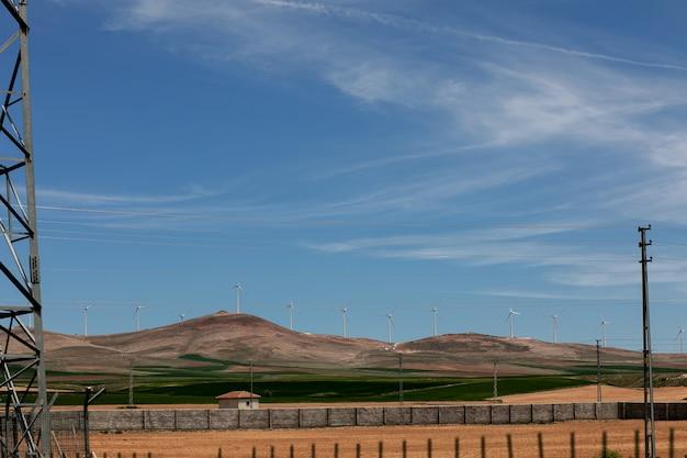 Elektrownia wiatrowa z turbinami na terenie górskim z błękitnym niebem w piękny jasny dzień