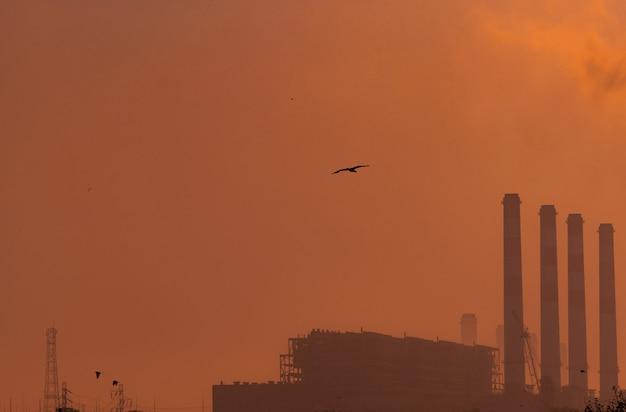 Elektrownia z pomarańczowym zmierzchu niebem i ptakami lata na niebie. koncepcja zanieczyszczenia powietrza. energia dla fabryki wsparcia na terenie przemysłowym. moc i energia