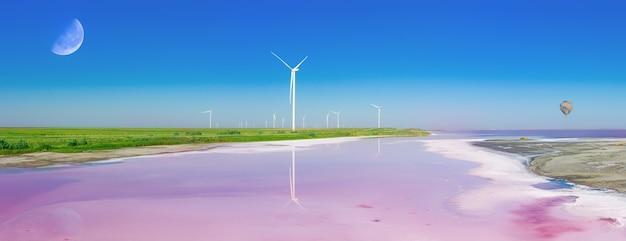 Elektrownie wietrzne ekologicznie na zielonym brzegu różowego jeziora