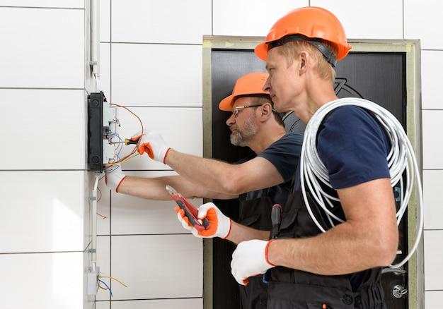 Elektrycy instalują okablowanie ścienne. łączą przewody w skrzynce połączeniowej.