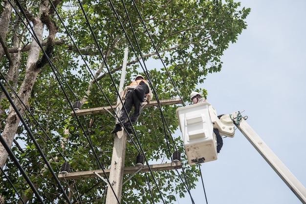 Elektrycy naprawiający drut