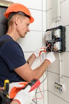 Elektrycy sprawdzają napięcie na zaciskach licznika elektrycznego.