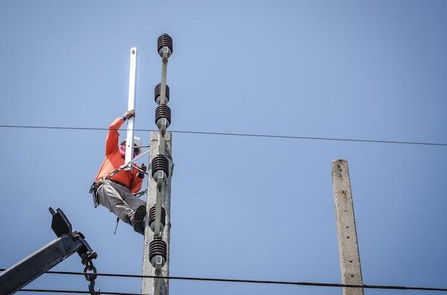 Elektrycy wspinają się po słupach elektrycznych, aby instalować i naprawiać linie energetyczne