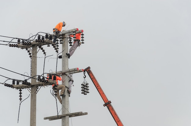 Elektrycy wspinają się po słupach elektrycznych, aby instalować i naprawiać linie energetyczne.