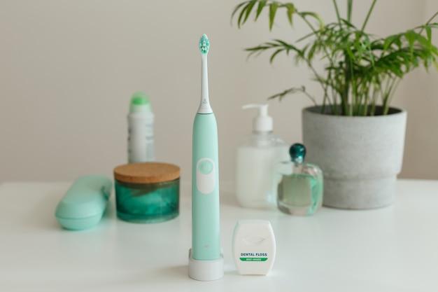 Elektryczna bezprzewodowa ultradźwiękowa szczoteczka do zębów z nicią dentystyczną stojąca w łazience