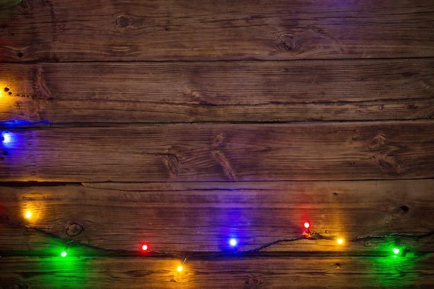 Elektryczna girlanda z wielokolorowymi żarówkami na drewnianej powierzchni, boże narodzenie i nowy rok w tle