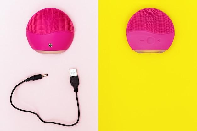 Elektryczna silikonowa szczotka do twarzy na zielonym i różowym papierze.
