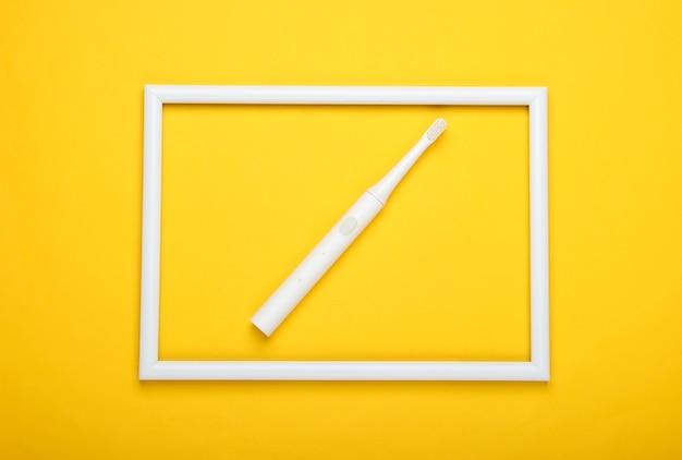 Elektryczna Szczoteczka Do Zębów Na żółtej Powierzchni Z Białą Ramką Premium Zdjęcia