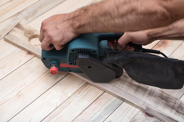 Elektryczna szlifierka taśmowa, szlifierka w męskiej dłoni. obróbka przedmiotu na jasnobrązowym drewnianym stole. ścieśniać