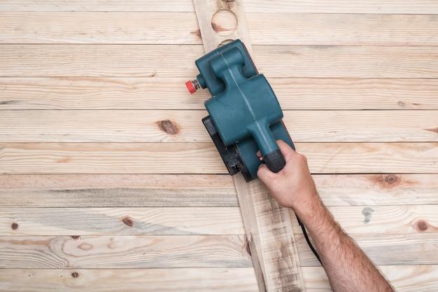 Elektryczna szlifierka taśmowa, szlifierka w męskiej dłoni. obróbka przedmiotu na jasnobrązowym drewnianym stole.