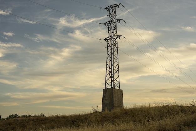 Elektryczna wieża przesyłu wysokiego napięcia na tle nieba o wschodzie słońca