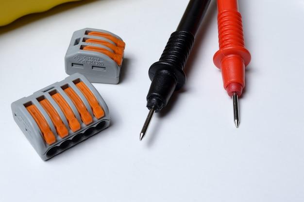 Elektryczne listwy zaciskowe i sondy multimetrowe na jasnym tle. zbliżenie.