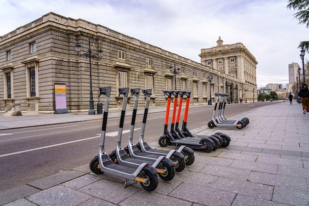 Elektryczne skutery zaparkowane na ulicy w pałacu królewskim w madrycie. hiszpania.