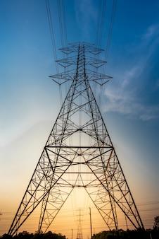 Elektryczne słupy i linie o zmierzchu lub wieże wysokiego napięcia na pięknym niebie
