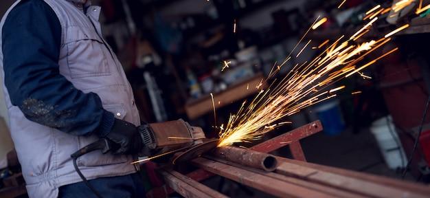Elektryczne szlifowanie kół na konstrukcji stalowej w fabryce.