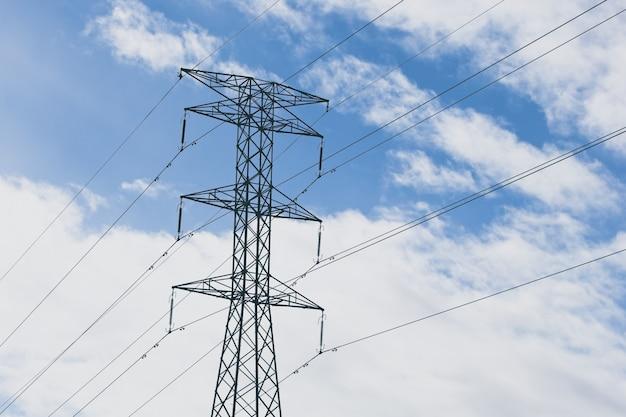 Elektryczne wieże z niebieskim pochmurnym niebem w tle