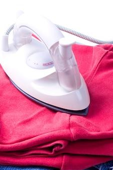 Elektryczne żelazko i stos ubrań na białym tle