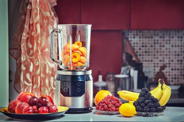 Elektryczny blender do robienia soków owocowych lub smoothie na drewnianym stole kuchennym.