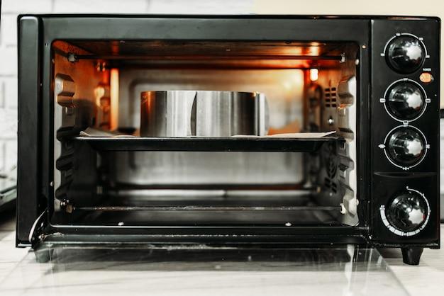 Elektryczny mini piekarnik do domowego gotowania, otwarte drzwi, widok zbliżenie.