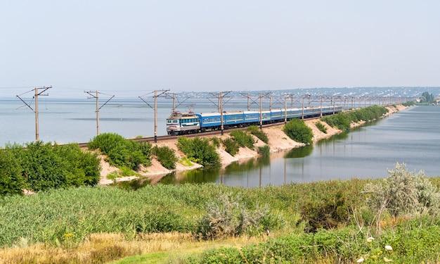 Elektryczny pociąg pasażerski przejeżdża przez rzekę dniepr na ukrainie
