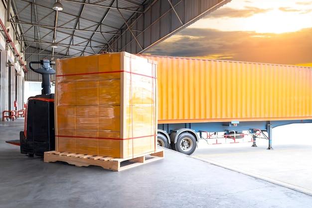 Elektryczny podnośnik paletowy z paletowym ładunkiem towarów ładunkiem z kontenerem