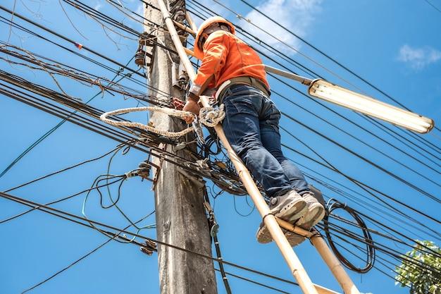 Elektryczny pracownik linemam wspina się po bambusowej drabinie, aby naprawić drut. inżynier telekomunikacyjny instalujący drut do internetu.