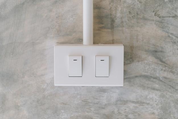 Elektryczny włącznik światła na tle ściany cementu