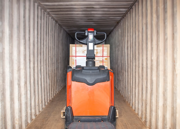 Elektryczny wózek widłowy podnośnik paletowy załaduj paletę ładunkową w kontenerze transportowym przesyłka towarowa dostawa towarowa ciężarówka