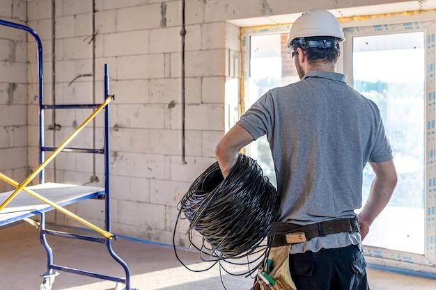 Elektryk bada rysunek konstrukcyjny, trzymając w ręku kabel elektryczny w miejscu pracy.