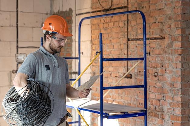 Elektryk bada rysunek konstrukcyjny, trzymając w ręku kabel elektryczny w miejscu pracy