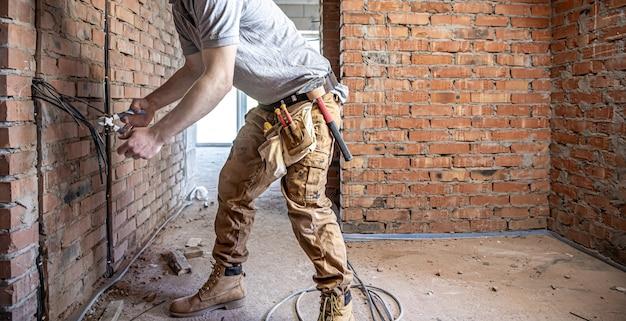 Elektryk budowlany przecina kabel napięciowy podczas naprawy