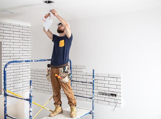 Elektryk budowniczy z brodą pracownikiem w białym kasku przy pracy, montaż lamp na wysokości. profesjonalista w kombinezonie z wiertłem na miejscu naprawy.