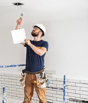 Elektryk budowniczy z brodą pracownikiem w białym kasku przy pracy, montaż lamp na wysokości. profesjonalista w kombinezonie z wiertłem na tle miejsca naprawy.