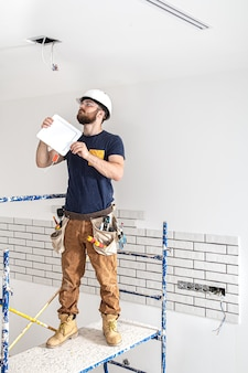 Elektryk budowniczy z brodą pracownikiem w białym kasku przy pracy, montaż lamp na wysokości.